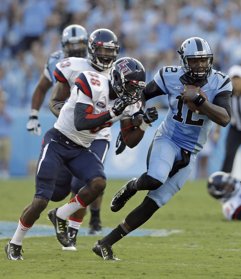 Photo - North Carolina quarterback Marquise Williams (12) runs the ball as Liberty's Alpha Jalloh (38) moves in for the tackle during the first half of an NCAA college football game in Chapel Hill, N.C., Saturday, Aug. 30, 2014. (AP Photo/Gerry Broome)