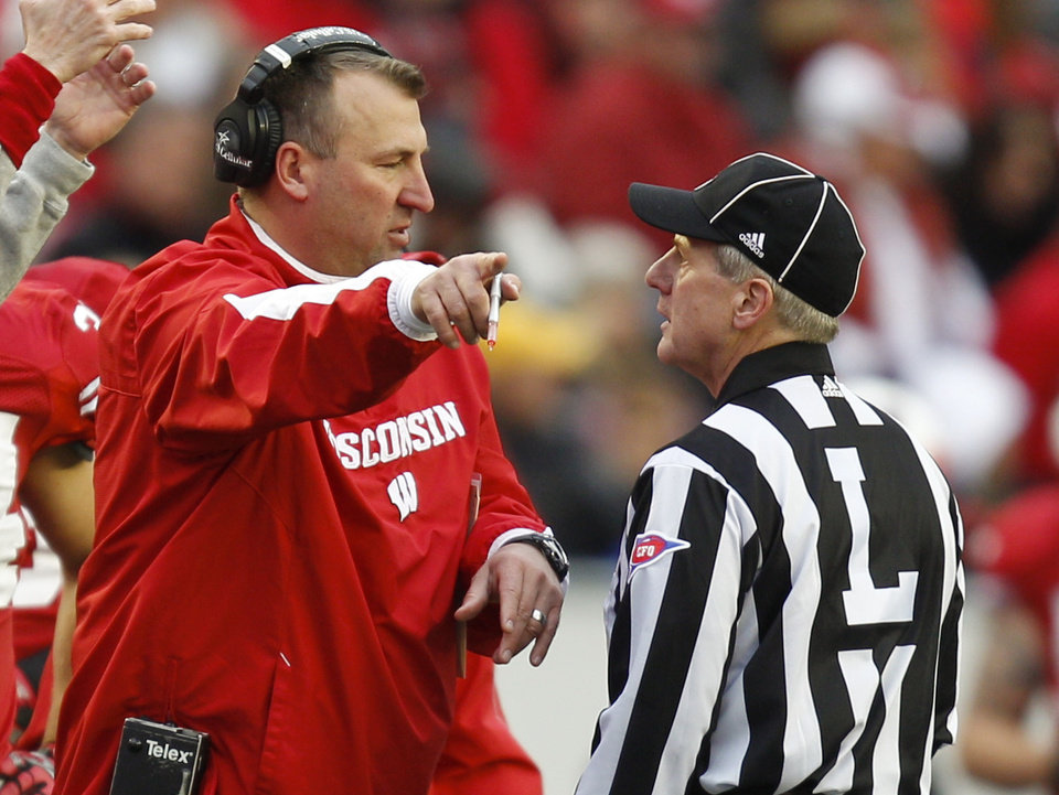 Photo -   Wisconsin coach Bret Bielema, left, talks with an official during the second half of an NCAA college football game against Illinois, Saturday, Oct. 6, 2012, in Madison, Wis. Wisconsin won 31-14. (AP Photo/Andy Manis)