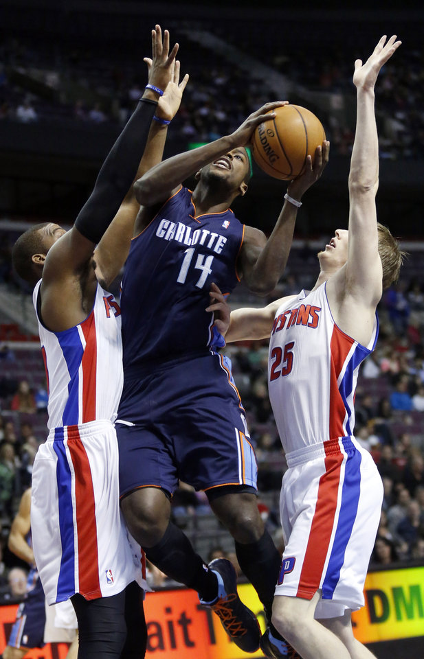 Photo - Charlotte Bobcats forward Michael Kidd-Gilchrist (14) goes to the basket between Detroit Pistons center Greg Monroe (10) and forward Kyle Singler (25) in the first half of an NBA basketball game, Sunday, Jan. 6, 2013, in Auburn Hills, Mich. (AP Photo/Duane Burleson)