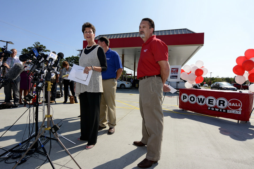 Photo - Lottery Executive Director Paula Harper Bethea and Murphy Express Regional manager Kip Fruge, right, speak to the media in front of Murphy Express store on Thursday, Sept. 19, 2013  in Lexington, S.C.  A $400 million winning ticket in the latest Powerball drawing was sold at the service station just off I-20 west of Columbia, officials with the South Carolina Education Lottery said Thursday.  Winners in South Carolina do not have to come forward publicly but Bethea noted that, in order to claim the winnings, the ticketholder must contact state lottery officials within 180 days.  (AP Photo/ Richard Shiro)