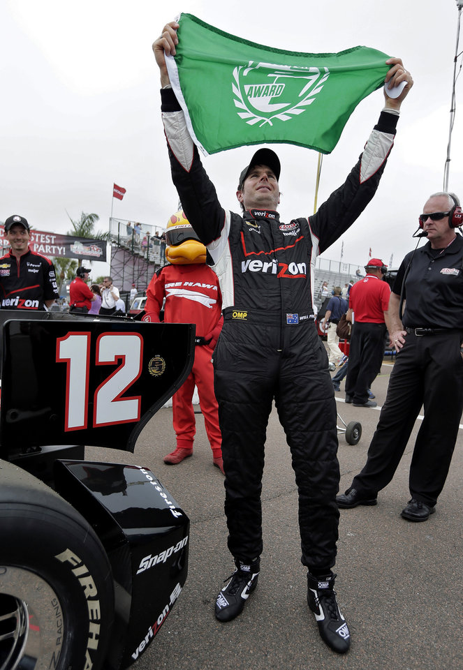 Will Power, of Australia, holds the pole award flag after qualifying for the IndyCar series Honda Grand Prix of St. Petersburg auto race Saturday, March 23, 2013, in St. Petersburg, Fla. Power will start first in Sunday's race. (AP Photo/Chris O'Meara)