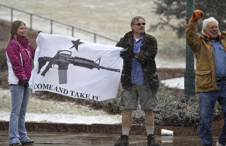 Opponents of proposed gun control bills being considered by the Colorado Legislature,  hold a sign depicting an assault rifle, displaying it to those passing in cars, in front of the State Capitol, in Denver, Monday March 4, 2013. State Senate committees began work on a package of gun-control measures that already have cleared the House which include limits on ammunition magazine sizes and expanded background checks to include private sales and online purchases. (AP Photo/Brennan Linsley)