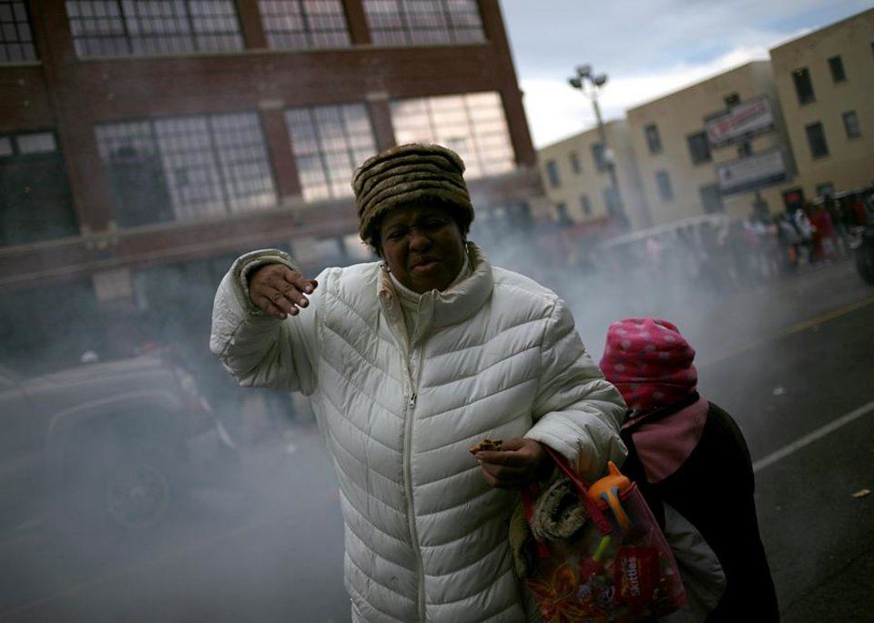 Photo -  Jennifer Birdine reacts to smoke and the smell of burning rubber as members of a motorcycle club spin their tires during the Martin Luther King Jr. Day Parade in Oklahoma City on Monday, Jan. 17, 2011. Photo by John Clanton, The Oklahoman ORG XMIT: KOD