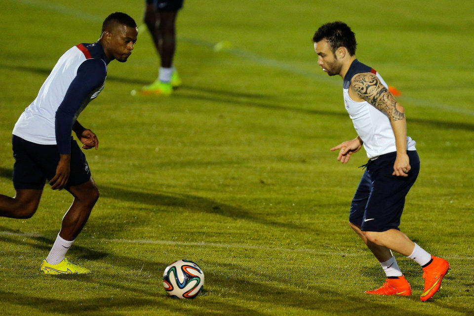Photo - France's Patrice Evra, left, and Mathieu Valbuena run on the field during an official training session at the Joao Havelange Olympic stadium, in Rio de Janeiro, Brazil, Tuesday, June 24, 2014. France will play its next game against Ecuador in group E of the 2014 soccer World Cup. A draw is enough to guarantee top spot for France, and would also send Ecuador through to the next round if Switzerland fails to beat Honduras in the other match. (AP Photo/David Vincent)