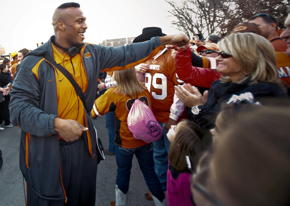Photo - Defensive end Richetti Jones and other Cowboy players greet fans in the team's pre-game walk before the Bedlam college football game between the University of Oklahoma Sooners (OU) and the Oklahoma State University Cowboys (OSU) at Boone Pickens Stadium in Stillwater, Okla., Saturday, Nov. 27, 2010. Photo by Chris Landsberger, The Oklahoman