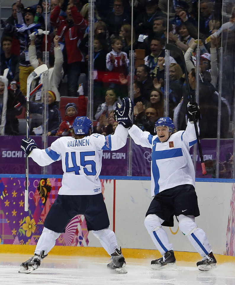 Photo - Finland defenseman Sami Vatanen celebrates with defenseman Juuso Hietanen after a goal against the USA during the second period of the men's bronze medal ice hockey game at the 2014 Winter Olympics, Saturday, Feb. 22, 2014, in Sochi, Russia. (AP Photo/Petr David Josek)