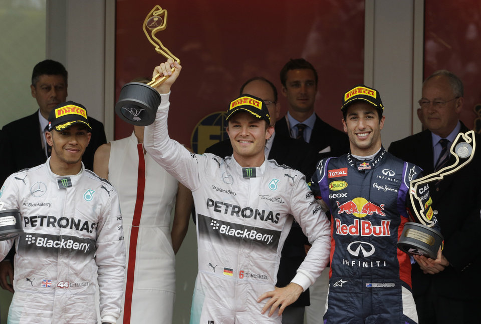 Photo - Mercedes driver Nico Rosberg of Germany, center, winner of the race is flanked by second place Mercedes driver Lewis Hamilton of Britain , left and third place Red Bull driver Daniel Ricciardo of Australia on the podium after the Monaco Formula One Grand Prix, at the Monaco racetrack, in Monaco, Sunday, May 25, 2014. At right in background Mercedes driver Nico Rosberg of Germany kisses Pricesse Charlene. Nico Rosberg won the Monaco Grand Prix from pole position on Sunday to take the overall championship lead from his teammate Lewis Hamilton, who finished second to give Mercedes a fifth straight 1-2 finish. The German driver clinched his second victory of the season and fifth of his career, making a strong start and holding off Hamilton to repeat his maiden GP win from pole here in Monaco last year. (AP Photo/Luca Bruno)