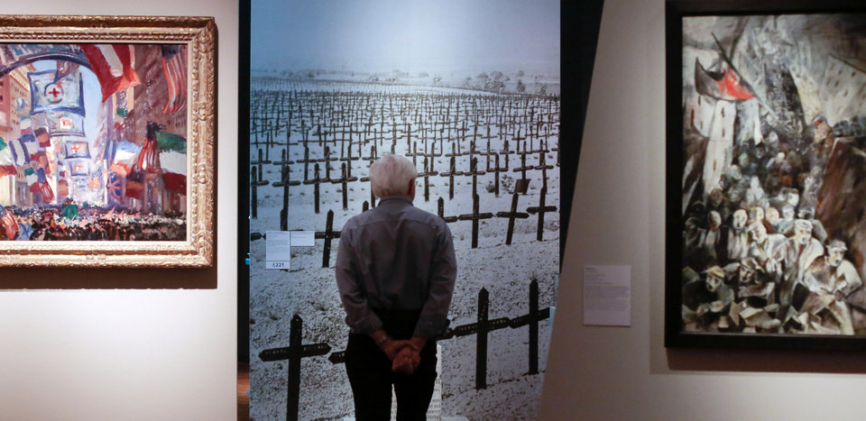 Photo - In this June 2, 2014 photo a visitor looks at a photo of a graveyard of fallen soldiers during an exhibition of World War I objects at the German Historical Museum in Berlin. At left, is the painting