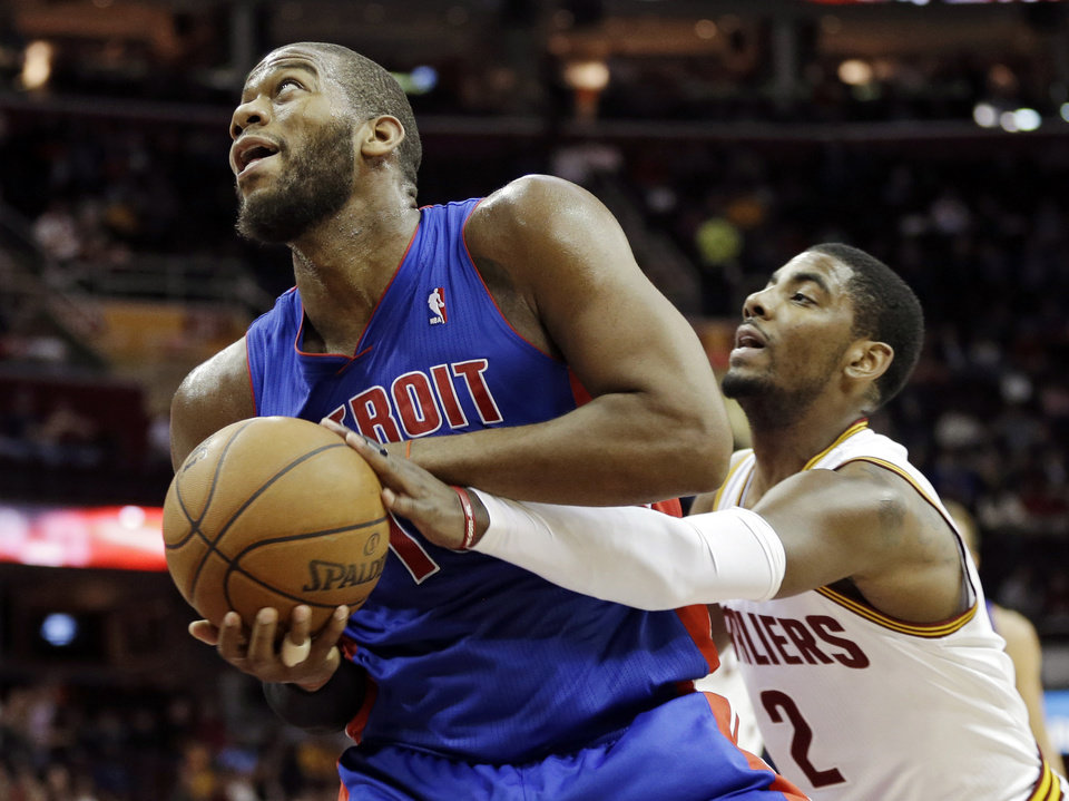 Photo - Cleveland Cavaliers' Kyrie Irving (2) tries to strip the ball from Detroit Pistons' Greg Monroe in the first quarter of an NBA basketball game on Wednesday, April 10, 2013, in Cleveland. (AP Photo/Mark Duncan)