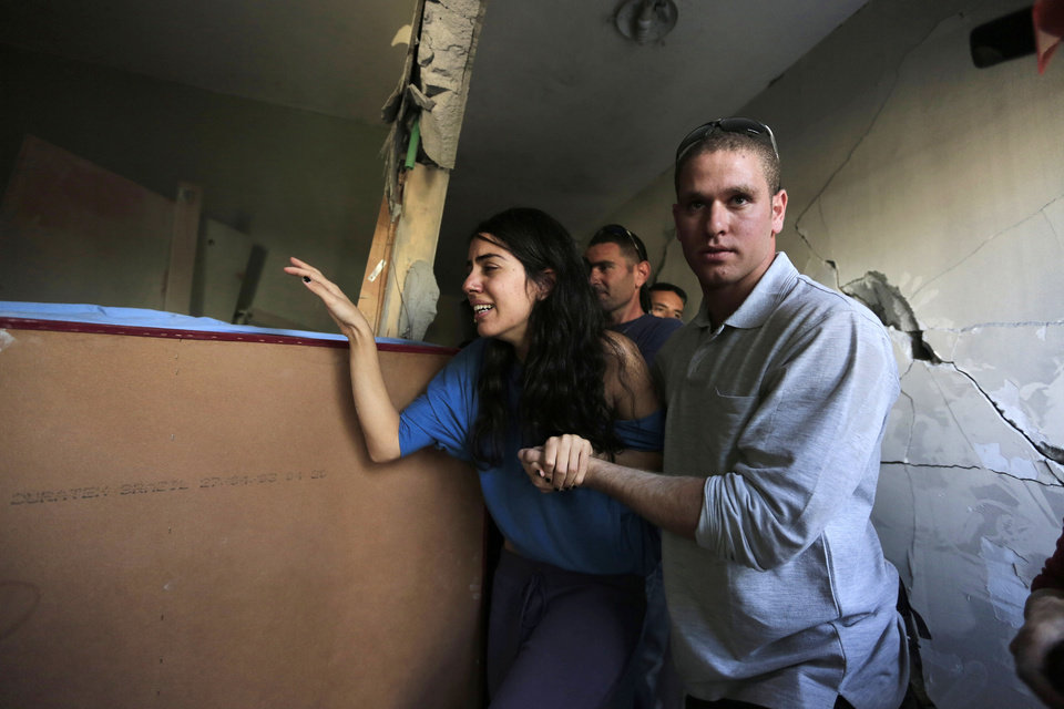 Photo -   Israelis Sapir, left, and her boyfriend Ron, right, last names not given, walk inside Sapir's home, hit by a rocket fired by militants from Gaza Strip, in the southern city of Beersheba, Israel, Tuesday, Nov. 20, 2012. Efforts to end a week-old convulsion of Israeli-Palestinian violence drew in the world's top diplomats on Tuesday, with President Barack Obama dispatching his secretary of state to the region on an emergency mission and the U.N. chief appealing from Cairo for an immediate cease-fire.(AP Photo/Tsafrir Abayov)