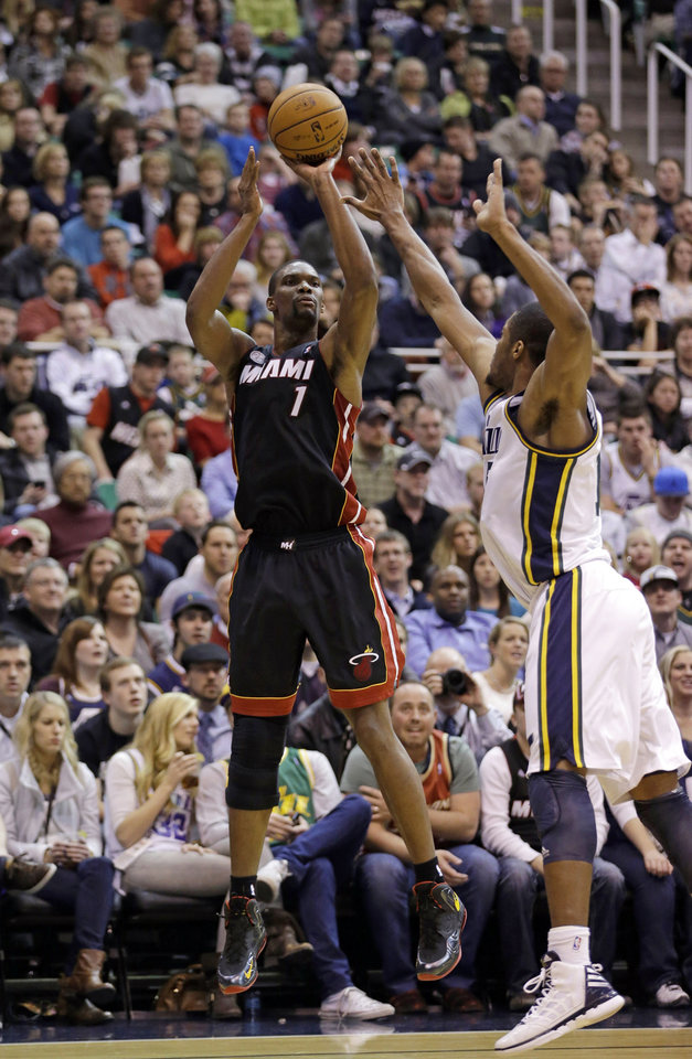 Photo - Miami Heat center Chris Bosh (1) shoots as Utah Jazz  forward Derrick Favors, right, defends in the second quarter during an NBA basketball game Monday, Jan. 14, 2013, in Salt Lake City.  (AP Photo/Rick Bowmer)