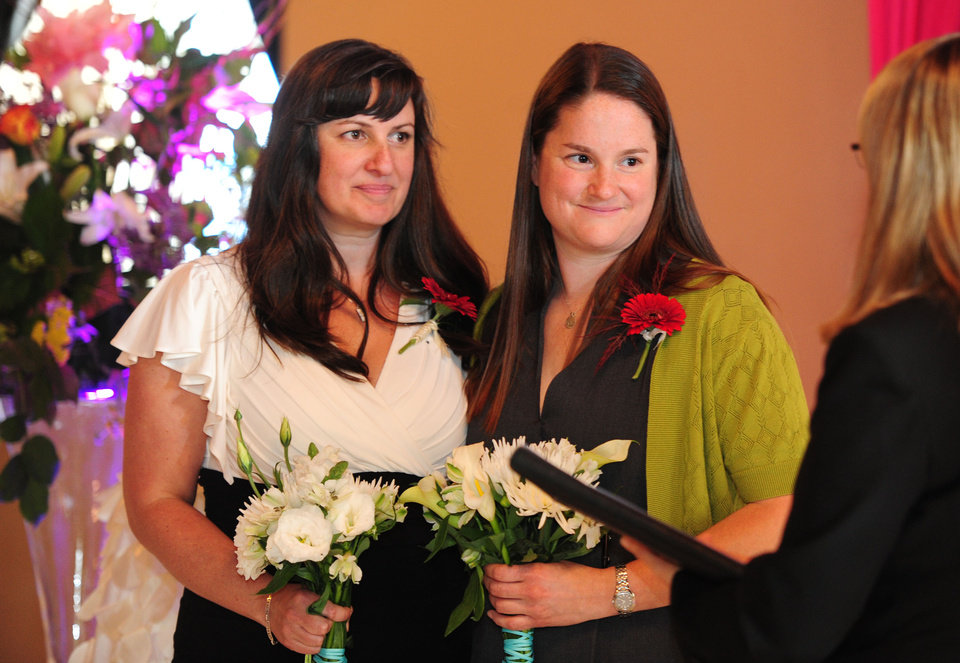 Photo - Julia Fraser, left, and Jessica Rohrbacher get married by Celebrant Holly Pruett at the Melody Ballroom in Portland, Ore., on Monday, May. 19, 2014. Federal Judge Michael McShane released an opinion on Oregon's Marriage Equality lawsuit that grants gay and lesbian couples the freedom to marry in Oregon. (AP Photo/Steve Dykes)