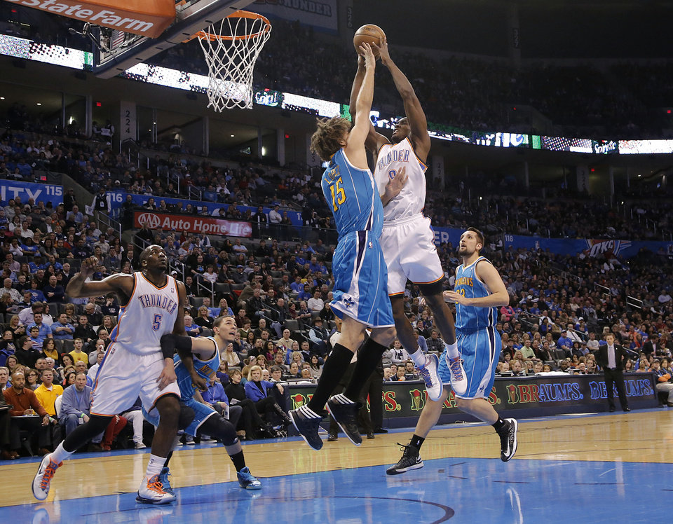 Photo - Oklahoma City Thunder's Serge Ibaka (9) drives against New Orleans Hornets' Robin Lopez (15) during the NBA basketball game between the Oklahoma City Thunder and the New Orleans Hornets at the Chesapeake Energy Arena on Wednesday, Feb. 27, 2013, in Oklahoma City, Okla. Photo by Chris Landsberger, The Oklahoman