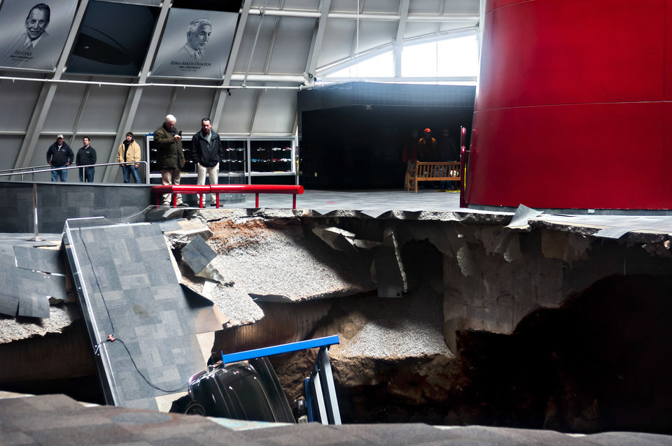 Photo - Officials view a sinkhole that opened up in the Skydome showroom, Wednesday, Feb. 12, 2014, at the National Corvette Museum in Bowling Green, Ky. Eight display cars were swallowed by the hole. (AP Photo/Daily News, Miranda Pederson)