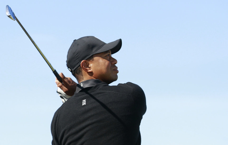 Photo - Tiger Woods of the US plays a shot on the 13th hole during a practice round ahead of the British Open Golf championship at the Royal Liverpool golf club, Hoylake, England, Tuesday July 15, 2014. The British Open starts on Thursday July 17. (AP Photo/Peter Morrison)