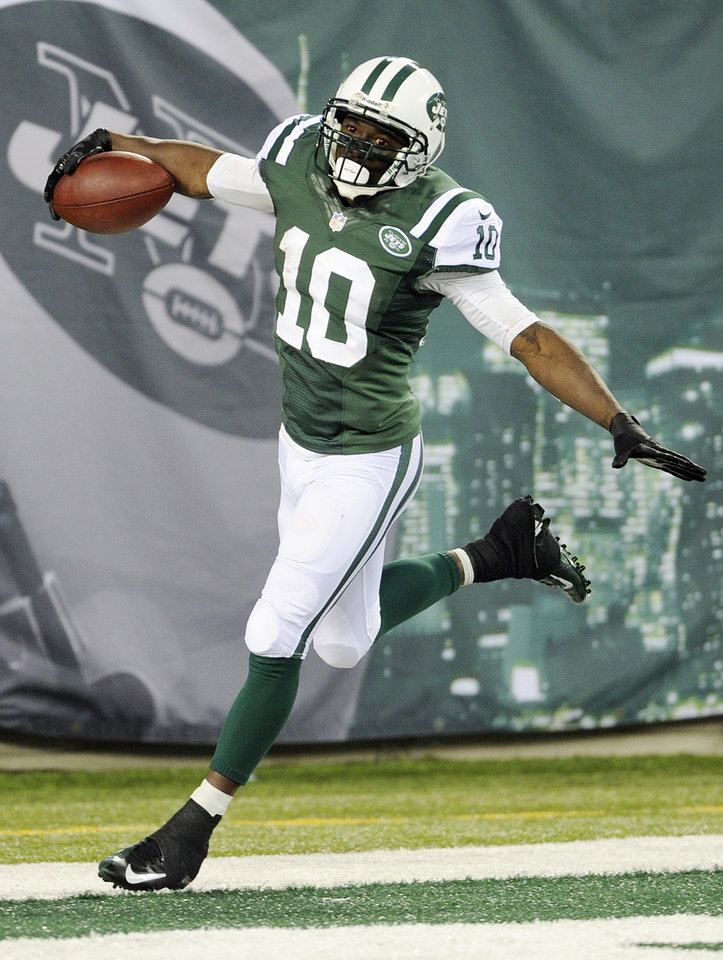 Photo - FILE - In this Sept. 22, 2013 file photo, New York Jets wide receiver Santonio Holmes (10) celebrates after scoring a touchdown during the second half of an NFL football game against the Buffalo Bills,  in East Rutherford, N.J.  The Jets have parted ways with Holmes, cutting the talented but injury-plagued playmaker after four seasons. The move Monday, March 10, 2014, which had been expected, saves the Jets $8.25 million, which Holmes was due to make as his base salary this season. (AP Photo/Bill Kostroun, File)
