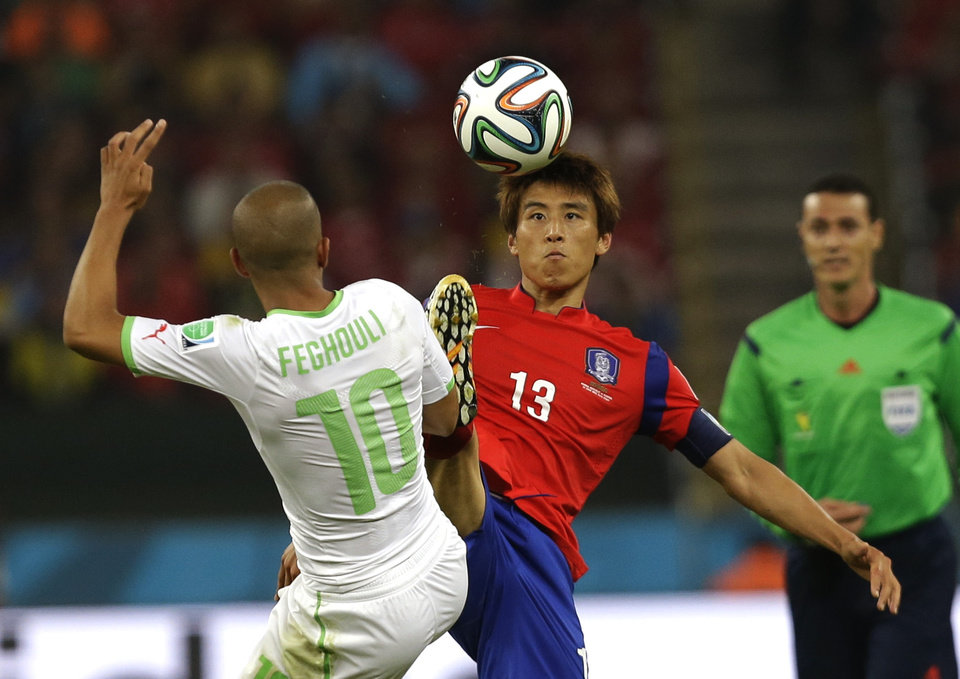 Photo - Algeria's Sofiane Feghouli and South Korea's Koo Ja-cheol  battle for the ball during the group H World Cup soccer match between South Korea and Algeria at the Estadio Beira-Rio in Porto Alegre, Brazil, Sunday, June 22, 2014. (AP Photo/Fernando Vergara)