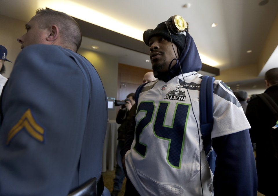 Photo - A member of the New Jersey state police escorts Seattle Seahawks running back Marshawn Lynch, right, through an area where a media availability was being held at the team's hotel Wednesday, Jan. 29, 2014, in Jersey City, N.J. The Seahawks and the Denver Broncos are scheduled to play in the Super Bowl XLVIII football game Sunday, Feb. 2, 2014. (AP Photo/Jeff Roberson)