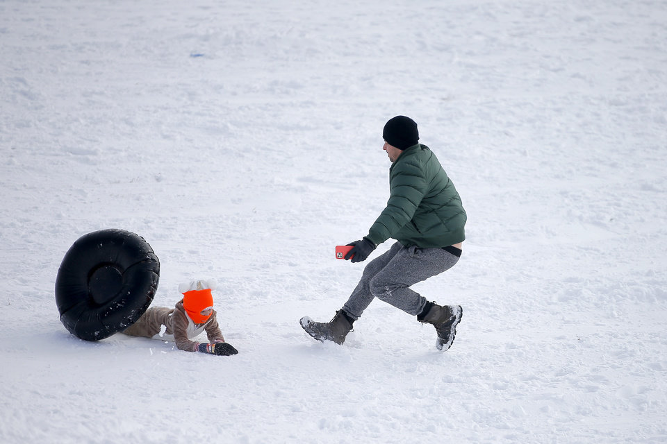 Photo - A sledder knocks down a man at the bottom of a hill along W Hefner Road in Oklahoma City after a winter storm dropped another layer of snow in Oklahoma City, Wednesday, Feb. 17, 2021. [Bryan Terry/The Oklahoman]