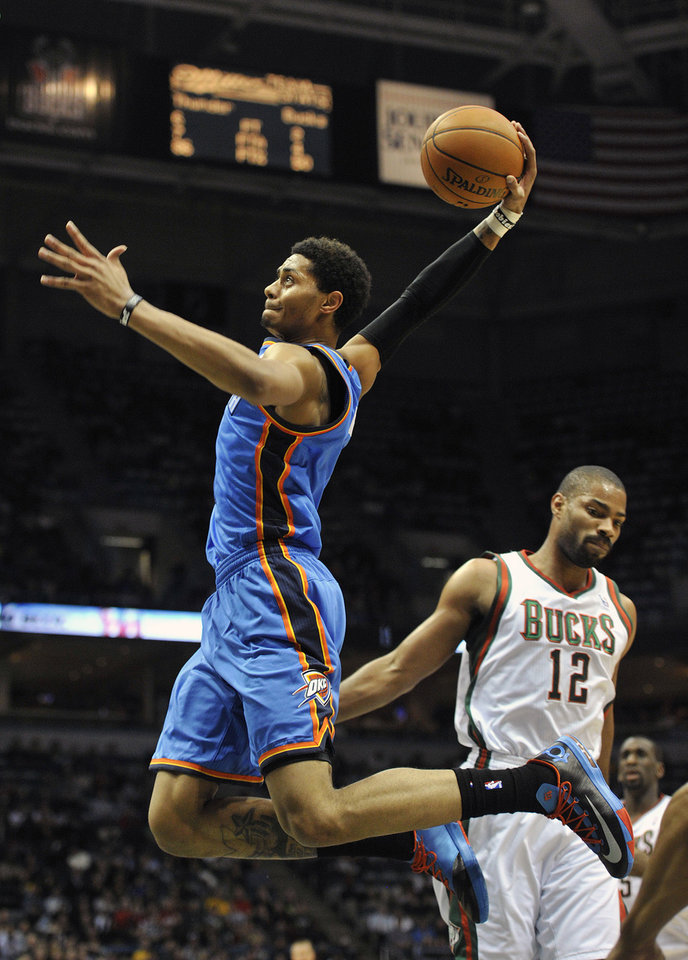 Photo - Oklahoma City Thunder's Jeremy Lamb dunks the ball over in front of Milwaukee Bucks' Gary Neal (12) during the first half of an NBA basketball game Saturday, Nov. 16, 2013, in Milwaukee. (AP Photo/Jim Prisching)