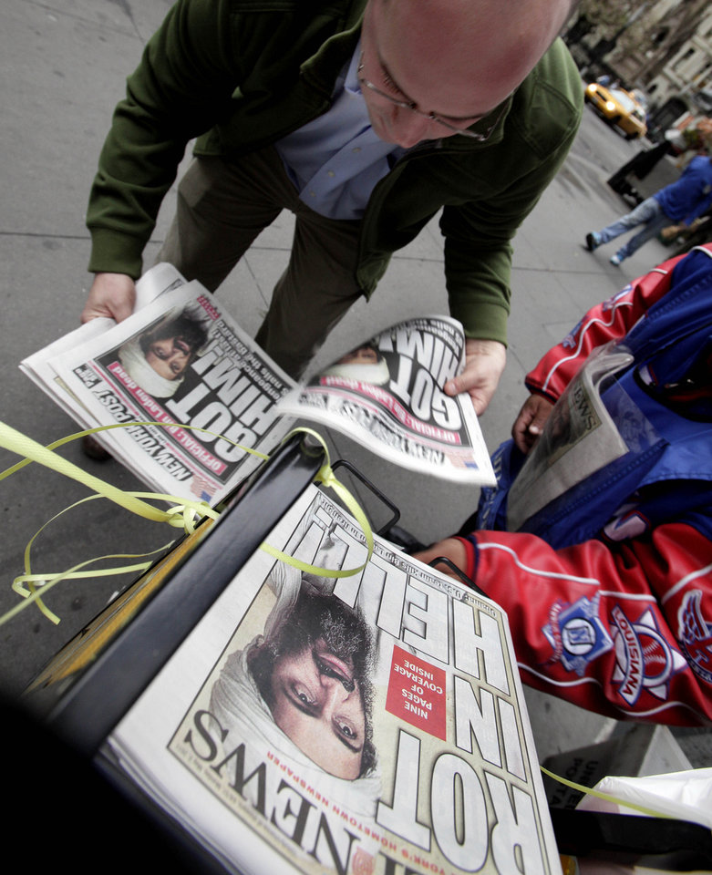 Photo - A man buys copies of newspapers in New York's Financial District featuring headlines of the death of Osama bin Laden, Monday, May 2, 2011. (AP Photo/Richard Drew)