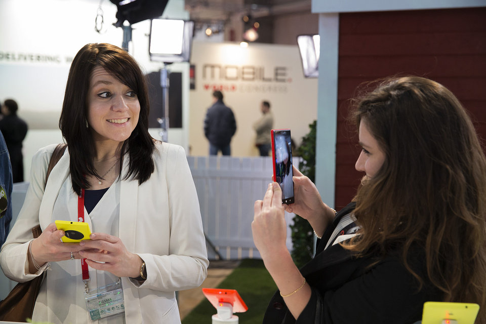 Photo - FILE - In this Tuesday, Feb. 25, 2014 file photo, a woman takes a picture with a Nokia Lumia 1520 phone as her friend smiles at the Mobile World Congress in Barcelona, Spain. The global wireless show that wraps in Barcelona on Thursday showed smartphone makers using software trickery to offset their camera weaknesses: inferior image sensors and lack of optical zoom lens. The companies are also making manipulating photos on the phone easier to learn than manually controlling DSLR cameras. (AP Photo/Marce Martinez, File)