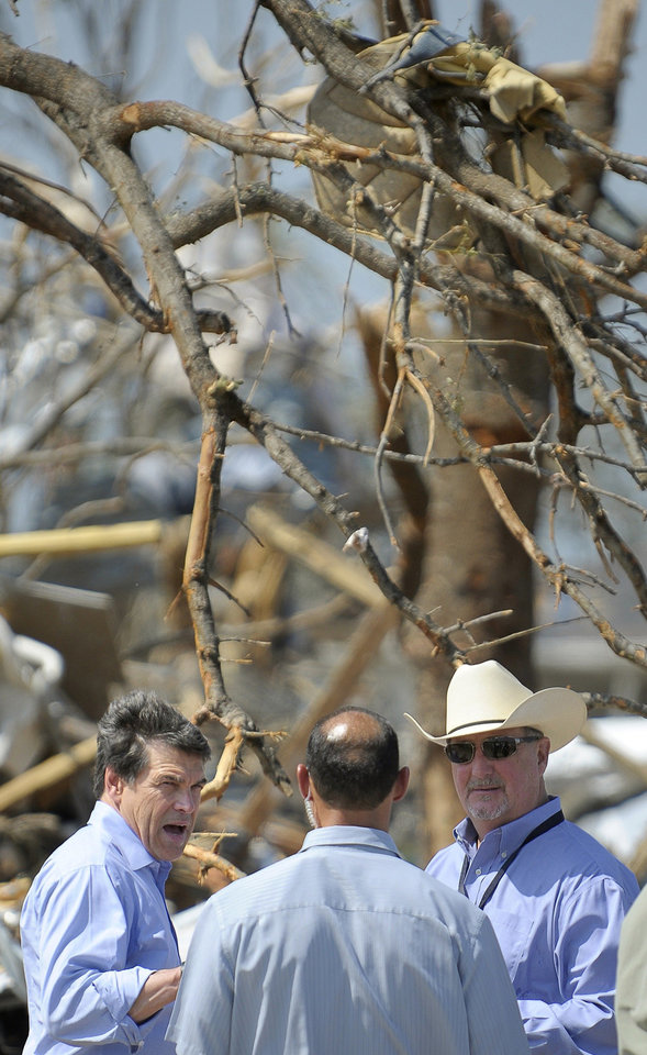 Photo - Texas Governor Rick Perry, left, tours the storm-damaged Rancho Brazos Estates subdivision near Granbury, Texas, on Friday May 17, 2013. On Wednesday, powerful storms produced 16 tornadoes in the area that left six dead. (AP Photo/The Fort Worth Star-Telegram, Max Faulkner)  MAGS OUT; (FORT WORTH WEEKLY, 360 WEST); INTERNET OUT