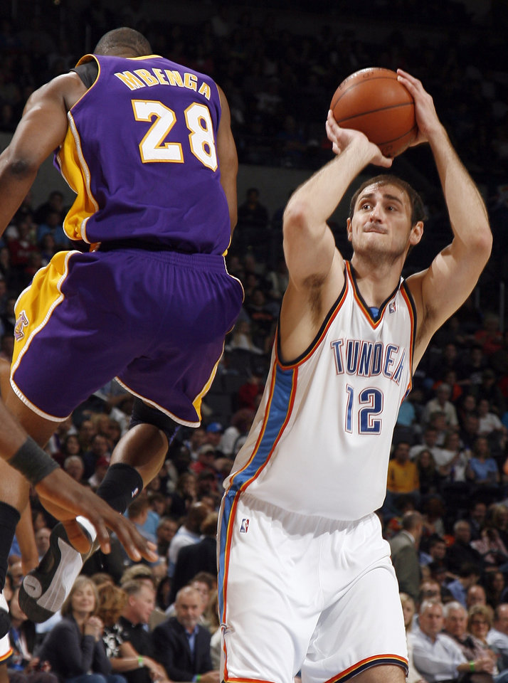 Photo - L.A. LAKERS: Oklahoma City's Nenad Krstic shoots as the Lakers's Didier Ilunga-Mbenga (28) jumps in front of him during the NBA basketball game between the Oklahoma City Thunder and the Los Angeles Lakers at the Ford Center, Tuesday, March 24, 2009, in Oklahoma City. PHOTO BY  SARAH PHIPPS, THE OKLAHOMAN ORG XMIT: KOD