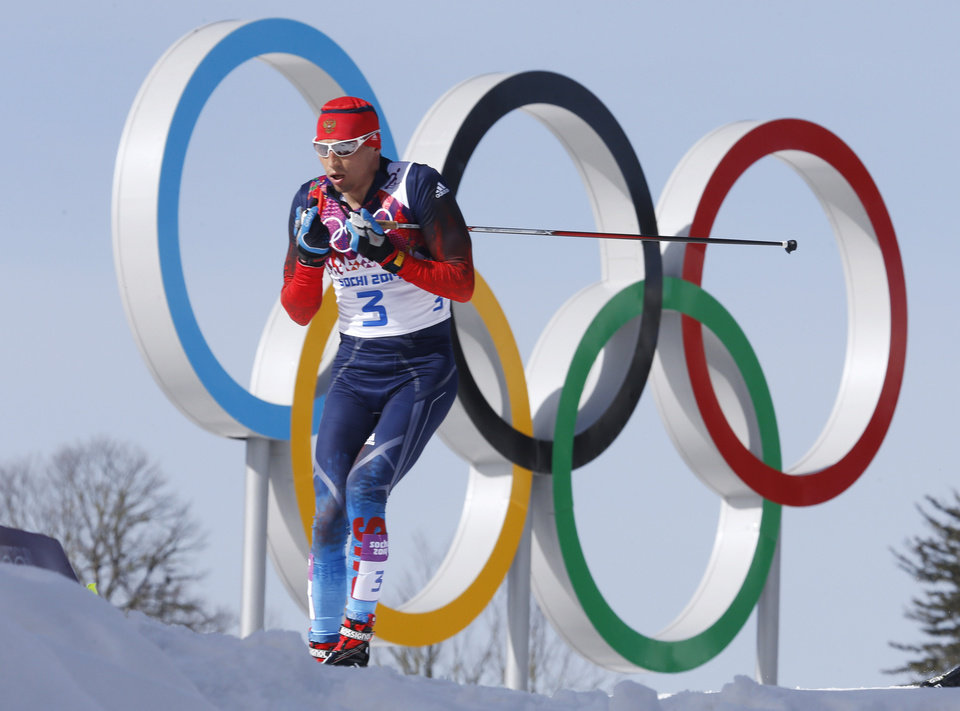 Photo - Russia's gold medal winner Alexander Legkov skis past the Olympic rings during the men's 50K cross-country race at the 2014 Winter Olympics, Sunday, Feb. 23, 2014, in Krasnaya Polyana, Russia. (AP Photo/Dmitry Lovetsky)