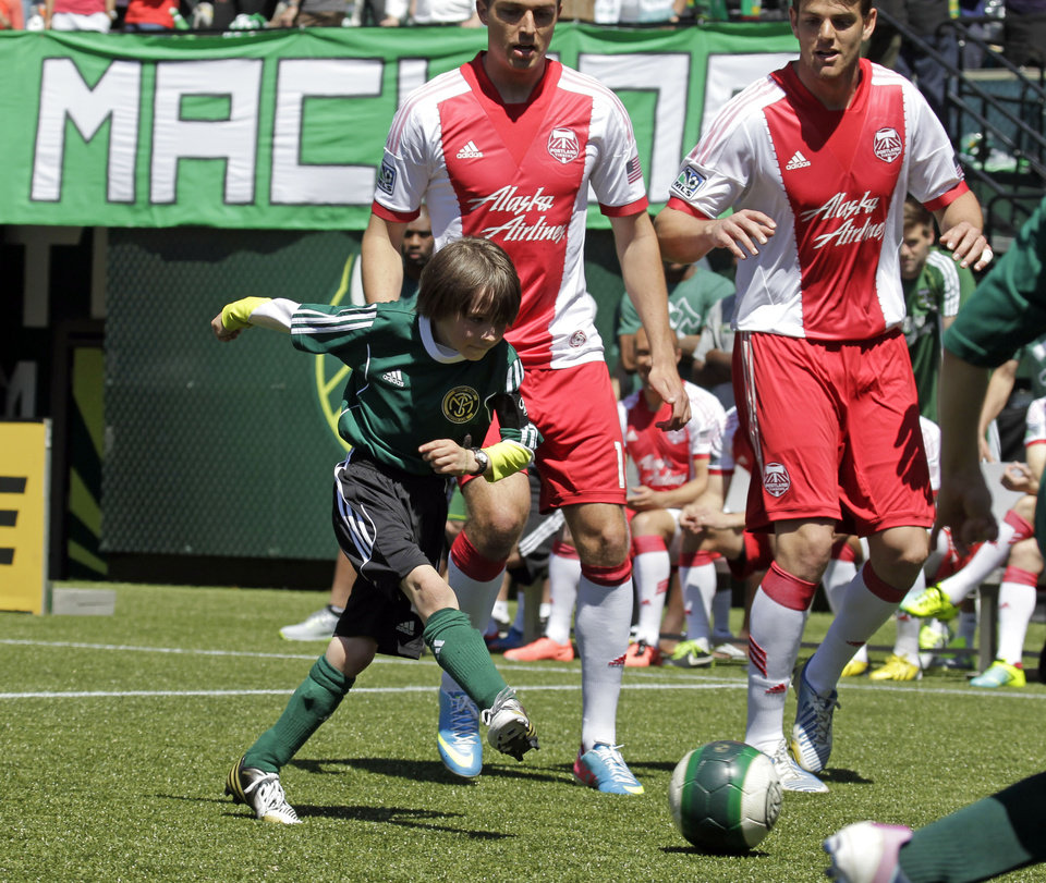 Photo - Atticus Lane-Dupre, 8, shoots for the winning goal as his team, the Green Machine, plays against the MLS Portland Timbers soccer team in Portland, Ore., Wednesday, May 1, 2013.  The Timbers and Make-A-Wish Oregon treated Atticus' team to a game at Jeld-Wen Field with more than 3,000 fans coming out to lend their support. Atticus missed the Green Machine's final match last fall because of cancer treatment.   (AP Photo/Don Ryan)