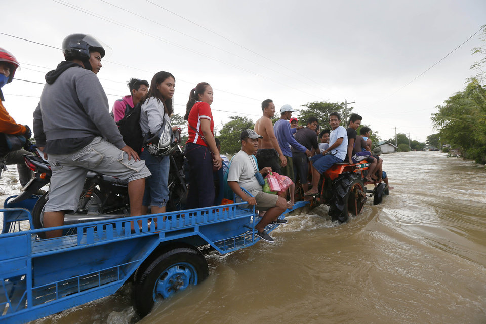 Photo - Commuters ride a farm tractor as it maneuvers through strong floodwaters from Typhoon Koppu along a highway in La Paz township, Tarlac province, in northern Philippines Tuesday, Oct. 20, 2015. Slow-moving Typhoon Koppu blew ashore with fierce wind in the northeastern Philippines early Sunday, toppling trees and knocking out power and communications and forcing the evacuation of thousands of villagers. (AP Photo/Bullit Marquez)