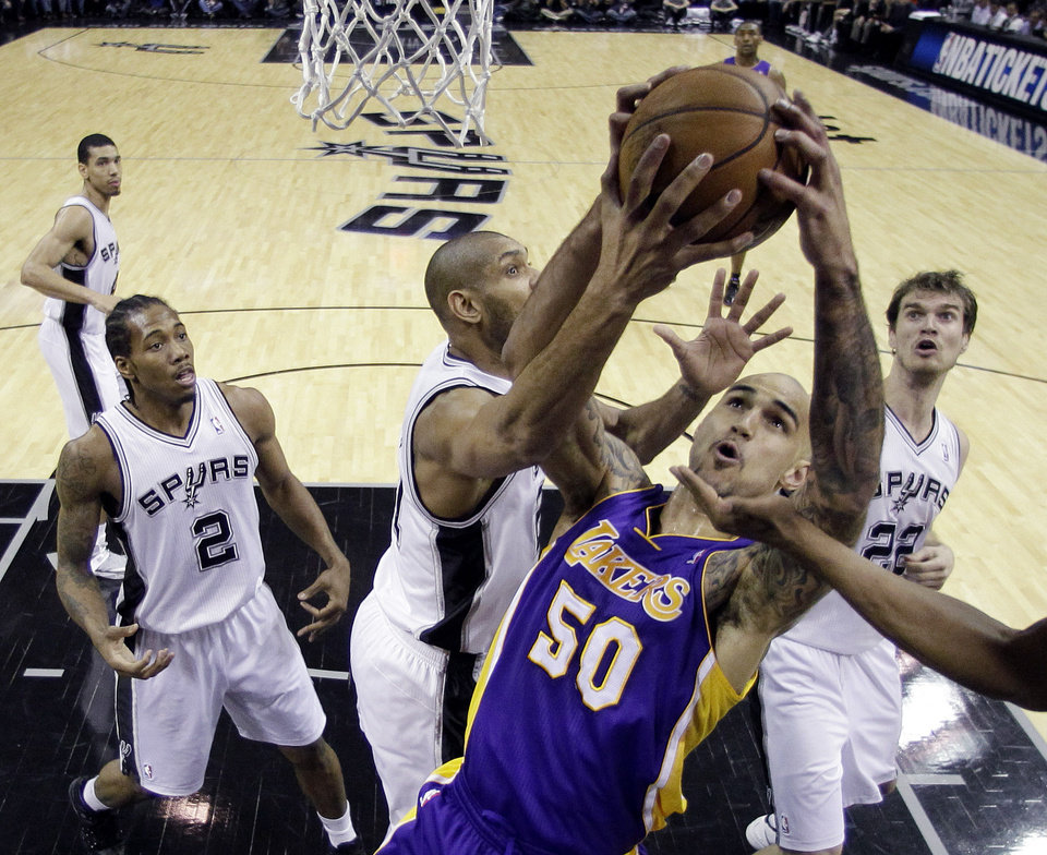 Photo - Los Angeles Lakers' Robert Sacre (50) is blocked by San Antonio Spurs' Tim Duncan, center, while trying to score during the first quarter of an NBA basketball game on Wednesday, Jan. 9, 2013, in San Antonio. (AP Photo/Eric Gay)