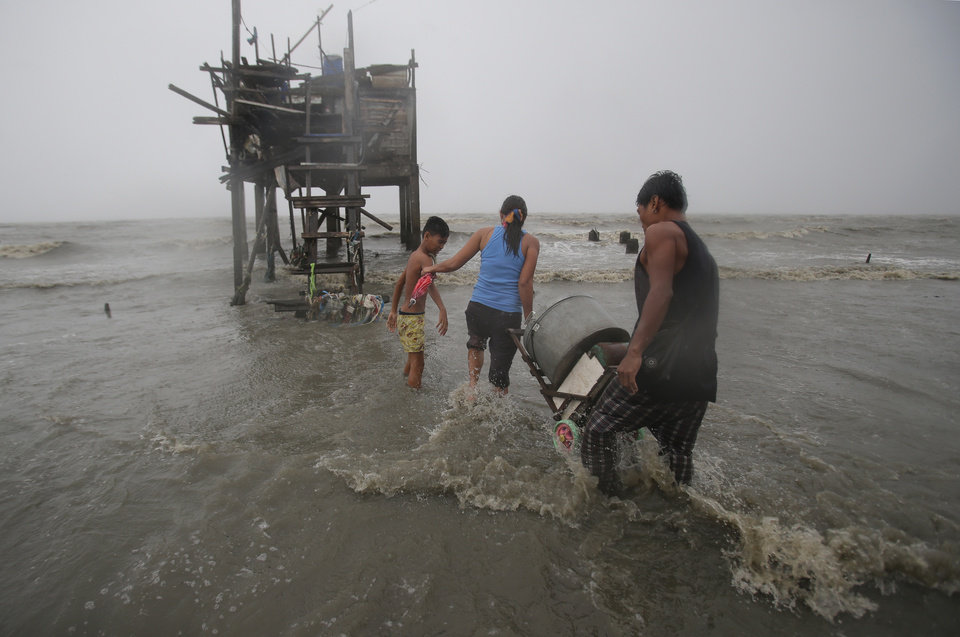 Photo - Residents carry their belongings towards their house on stilts as strong winds and rains caused by Typhoon Koppu hits the coastal town of Navotas, north of Manila, Philippines on Sunday, Oct. 18, 2015.  Slow-moving Typhoon Koppu blew ashore with fierce wind in the northeastern Philippines early Sunday, toppling trees and knocking out power and communications. (AP Photo/Aaron Favila)