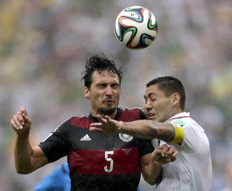 Germany\'s Mats Hummels heads the ball with United States\' Clint Dempsey during the group G World Cup soccer match between the United States and Germany at the Arena Pernambuco in Recife, Brazil, Thursday, June 26, 2014. (AP Photo/Julio Cortez)
