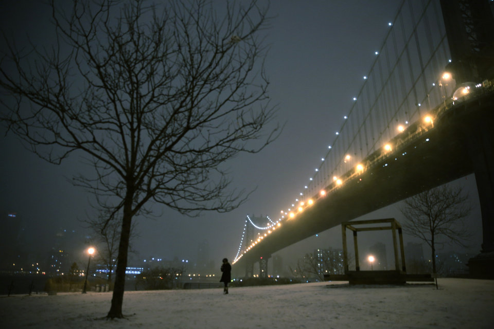 Photo - A woman walks through a park on the waterfront in Brooklyn near the Manhattan Bridge during a winter storm in New York, Thursday, Jan. 2, 2014. The storm is expected to bring snow, stiff winds and punishing cold into the Northeast. (AP Photo/Peter Morgan)