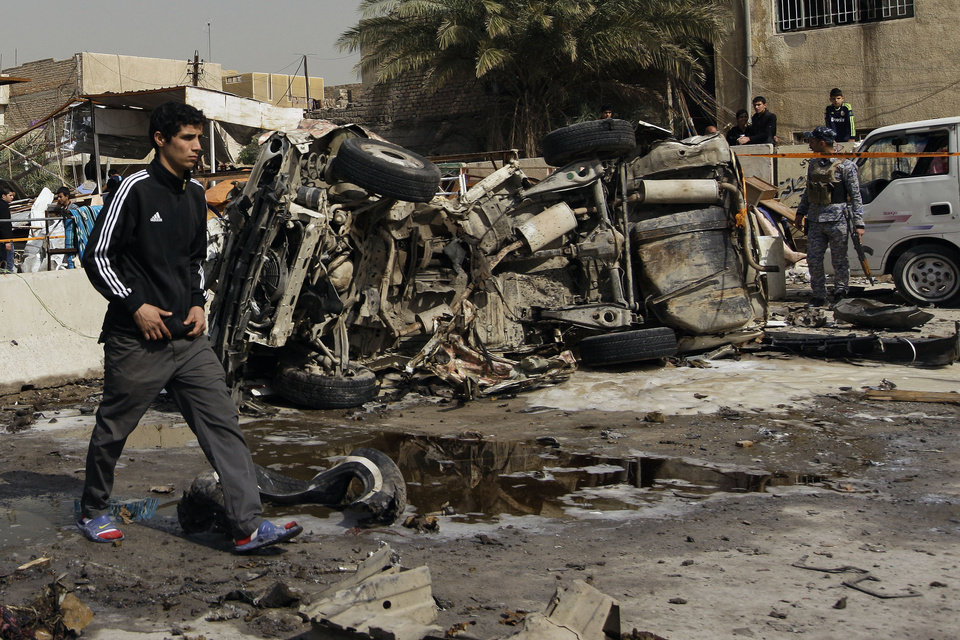 Photo - An Iraqi walks past the scene of a car bomb attack in the Ameen neighborhood of eastern Baghdad, Iraq, Sunday, Feb. 17, 2013. A series of car bombs exploded within minutes of each other as Iraqis were out shopping in and around Baghdad on Sunday, killing and wounding scores of people, police said. (AP Photo/ Khalid Mohammed)