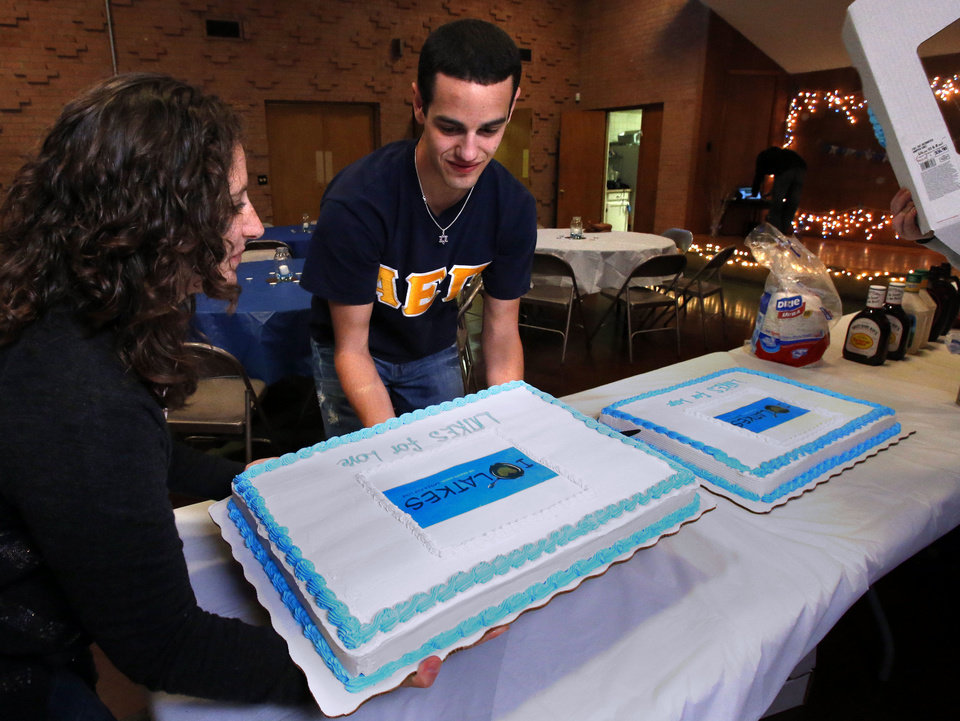 Photo - University of Oklahoma students Rebekah Martin and Jake Fuller set out cakes at the OU Hillel Foundation's annual