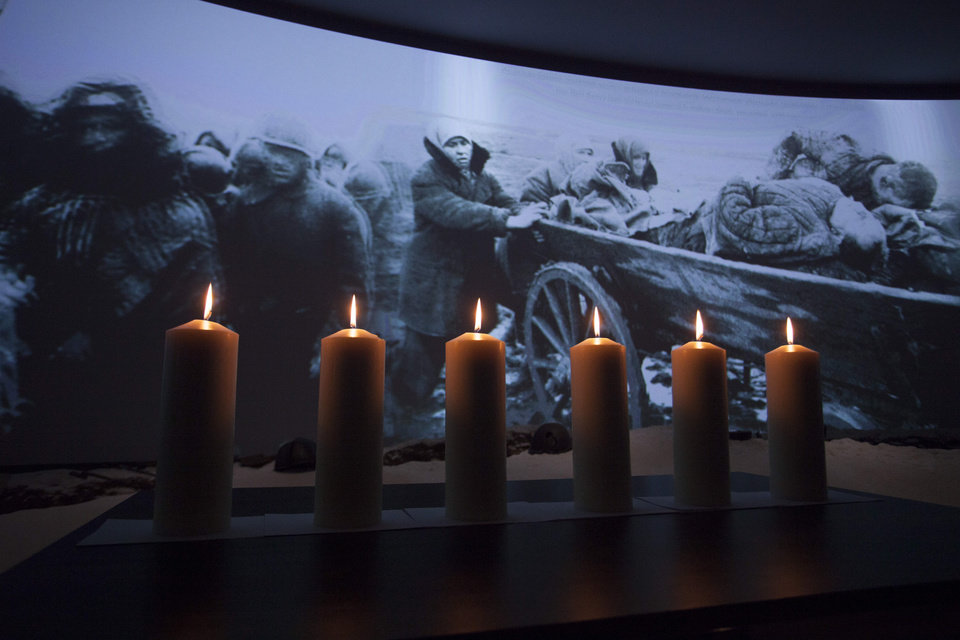 Photo - Memorial candles are lit in front of a photo taken during WWII showing refugees fleeing from the Nazis at a ceremony marking International Holocaust Remembrance Day in Russia's first Jewish Museum in Moscow, Russia, Sunday, Jan. 27, 2013. (AP Photo/Alexander Zemlianichenko Jr)