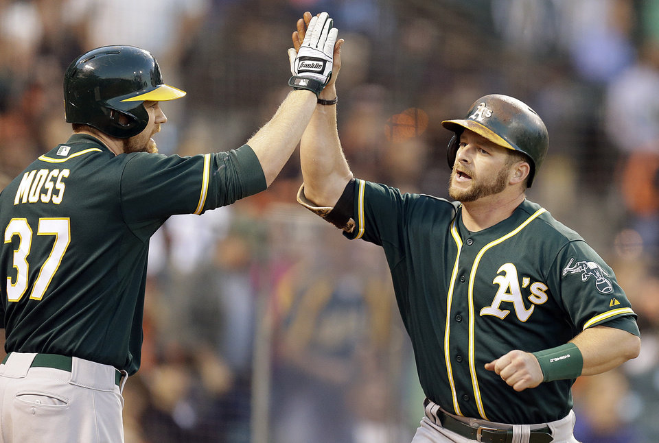 Photo - Oakland Athletics' Stephen Vogt, right, is congratulated by Brandon Moss (37) after Vogt hit a home run off San Francisco Giants' Matt Cain in the fourth inning of a baseball game Wednesday, July 9, 2014, in San Francisco. (AP Photo/Ben Margot)