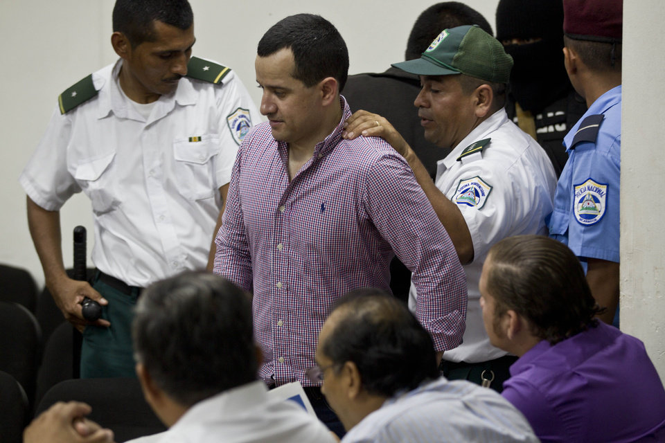 Photo -   Henry Farinas is escorted by police to the reading of his sentence on charges of money laundering in Managua, Nicaragua, Friday, Oct. 12, 2012. A Nicaraguan judge handed down a 30-year sentence for money-laundering to Farinas who was allegedly targeted when gunmen killed Argentine folk singer Facundo Cabral. Prosecutors say a trafficking gang believed Farinas had betrayed it and tried to kill him as he accompanied Cabral in a vehicle after a July 2011 concert in Guatemala that Farinas organized. (AP Photo/Esteban Felix)