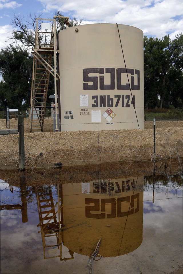 Photo - In this Wednesday, Sept. 18, 2013 photo, an oil well pump site is reflected in flood waters near Greeley, Colo. Colorado's floods shut down hundreds of natural gas and oil wells, spilled oil from one tank and sent inspectors into the field looking for more pollution. Besides the environmental impact, flood damage to roads, railroads and other infrastructure will affect the region's energy production for months to come. Analysts warn that images of flooded wellheads will increase public pressure to impose restrictions on drilling techniques such as fracking.(AP Photo/Ed Andrieski)