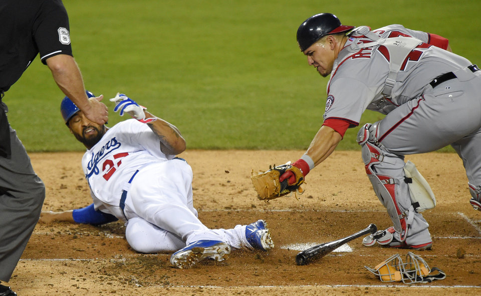 Photo - Los Angeles Dodgers' Matt Kemp, center, is tagged out at home by Washington Nationals catcher Wilson Ramos as he tried to score on a bunt by Carl Crawford during the fourth inning of a baseball game Tuesday, Sept. 2, 2014, in Los Angeles. (AP Photo/Mark J. Terrill)