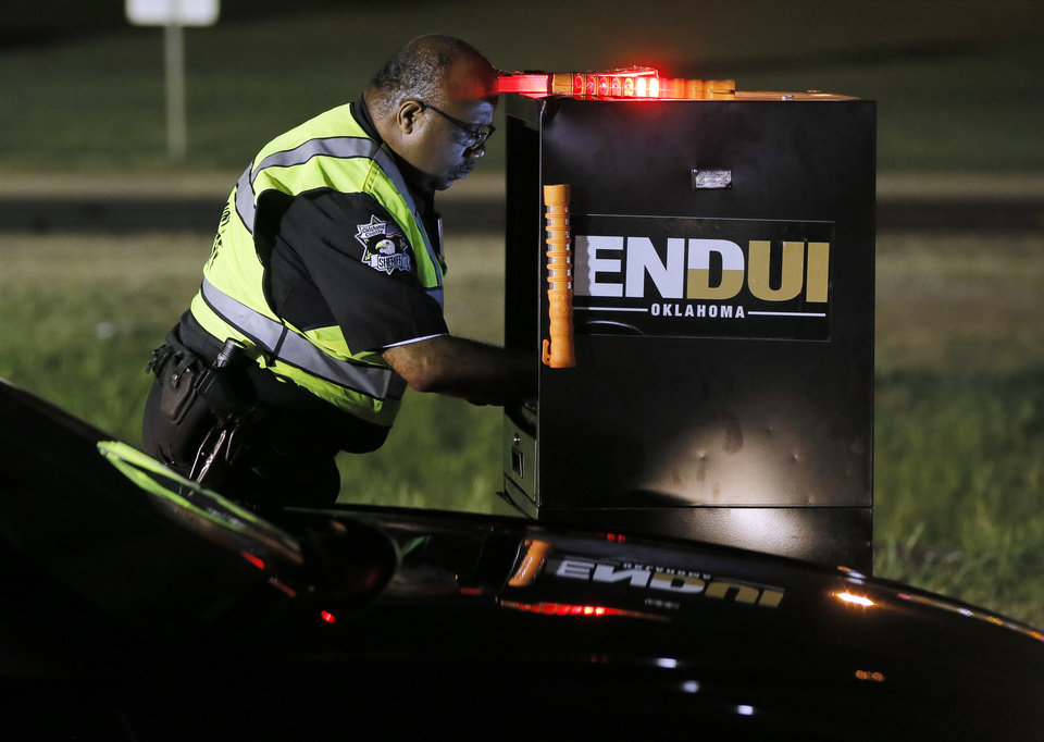 Photo -  Oklahoma County sheriff's Deputy Marvin Sampson looks up a driver's information on a computer at an ENDUI checkpoint on westbound Reno Avenue. [Photo by Nate Billings, The Oklahoman]