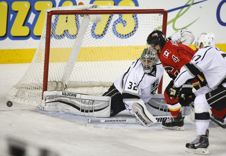 Photo - Los Angeles Kings goalie Jonathan Quick, left, kicks the puck away as Calgary Flames' Kris Russell chases it during the second period of an NHL hockey game Thursday, Feb. 27, 2014, in Calgary, Alberta. (AP Photo/The Canadian Press, Jeff McIntosh)