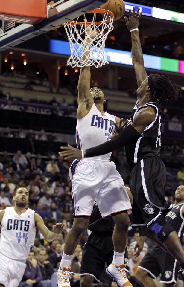 Photo - Charlotte Bobcats' Ramon Sessions (7) has his shot blocked by Brooklyn Nets' Gerald Wallace (45) during the first half of an NBA basketball game in Charlotte, N.C., Wednesday, March 6, 2013. (AP Photo/Bob Leverone)
