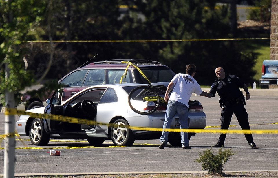 Photo -   A man shakes hands with a law enforcement officer after picking up his car at the parking lot of Century Aurora 16 movie theater Saturday, July 21, 2012 in Aurora , Colo. Twelve people were killed and dozens were injured in the attack early Friday at the packed theater during a showing of the Batman movie,