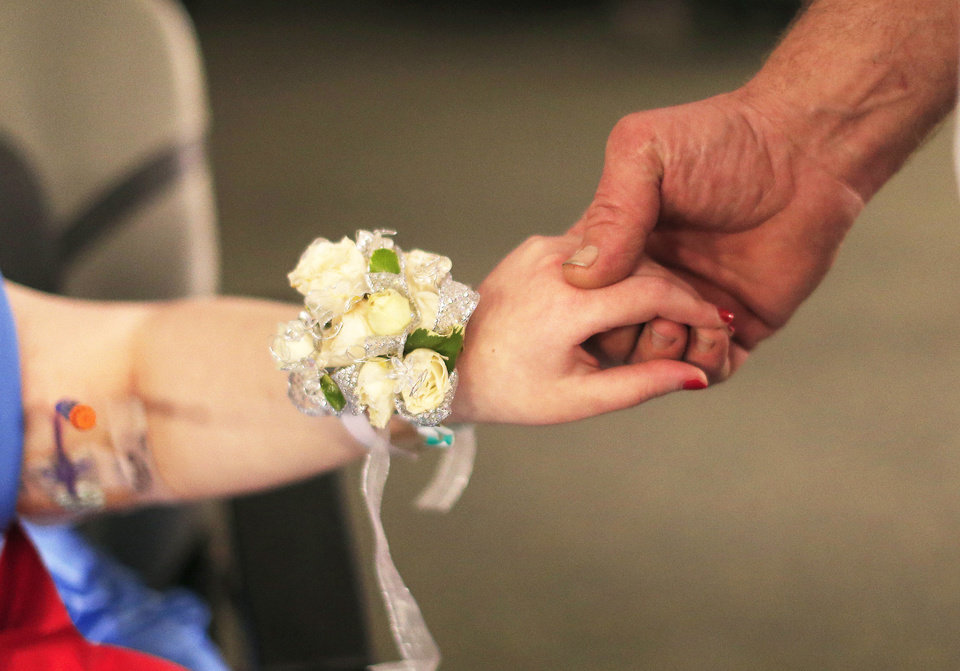 Hayle Savage holds the hand of her soon-to-be stepfather, Darin McDaniel, as she dances at The Children's Center in Bethany. Photo by Sarah Phipps, The Oklahoman <strong>SARAH PHIPPS - SARAH PHIPPS</strong>