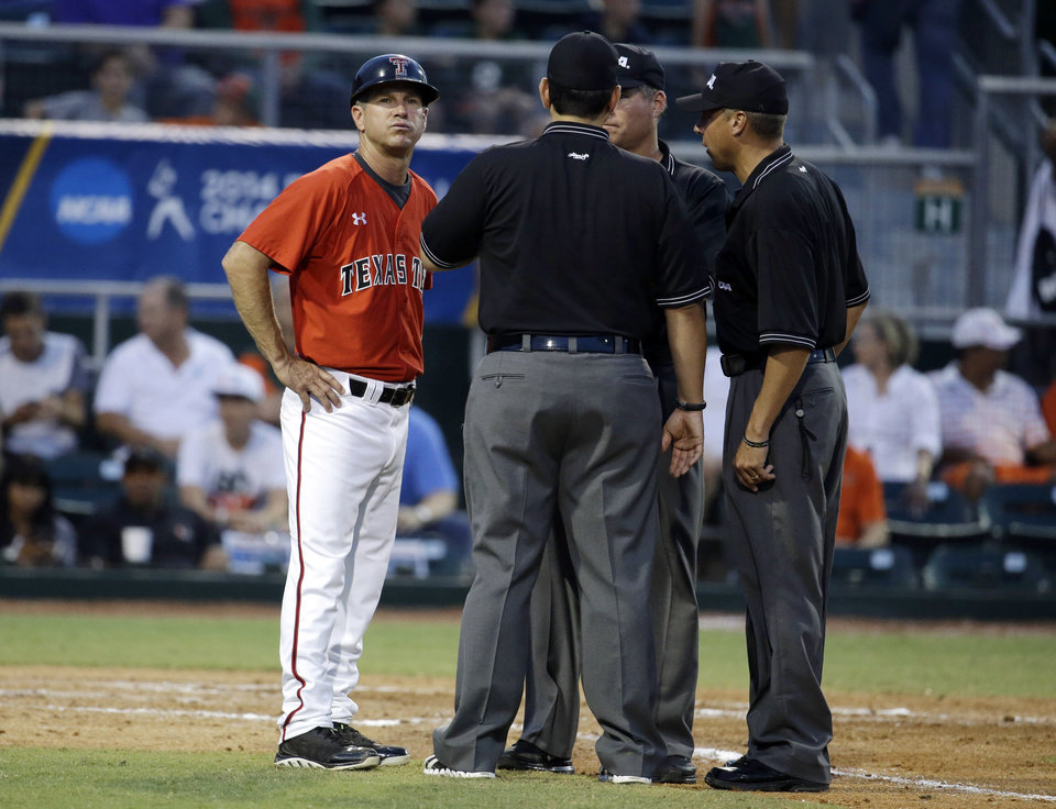 Photo - Texas Tech head coach Tim Tadlock, left, talks with the umpires after the benches cleared with Miami and Texas Tech in the third inning during an NCAA college baseball regional tournament in Coral Gables, Fla., Sunday, June 1, 2014.  (AP Photo/Lynne Sladky)