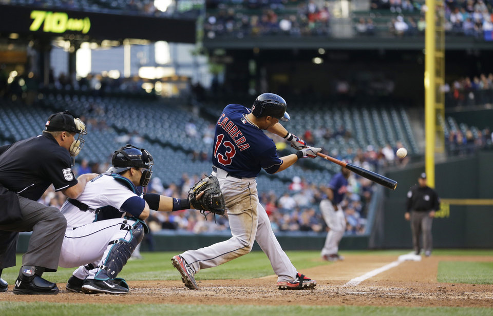 Photo - Cleveland Indians' Asdrubal Cabrera hits a sacrifice fly to score Michael Bourn (not shown) in the fifth inning of a baseball game against the Seattle Mariners, Saturday, June 28, 2014, in Seattle. (AP Photo/Ted S. Warren)