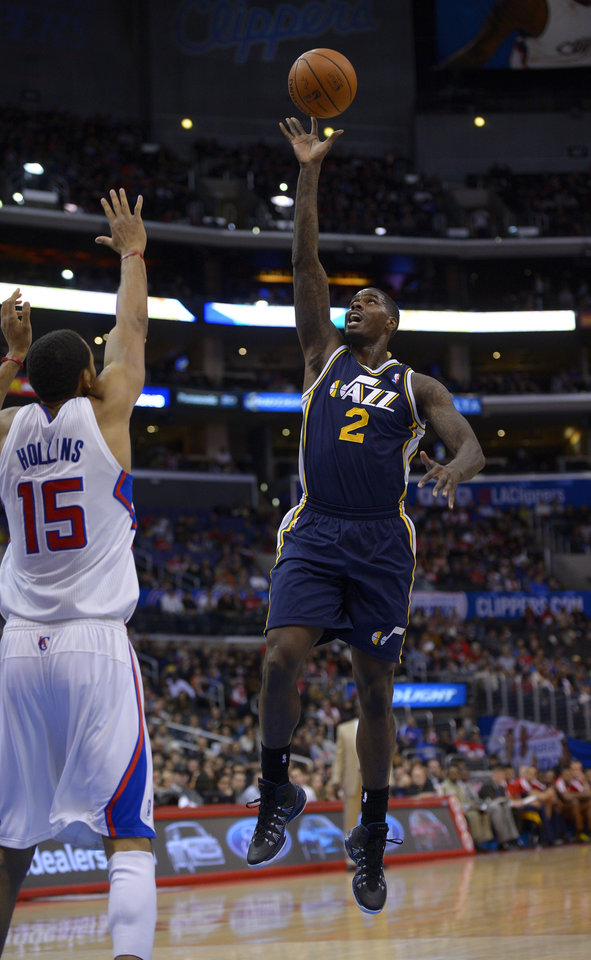 Photo - Utah Jazz forward Marvin Williams, right, shoots as Los Angeles Clippers center Ryan Hollins defends during the first half of an NBA basketball game on Saturday, Feb. 1, 2014, in Los Angeles. (AP Photo/Mark J. Terrill)